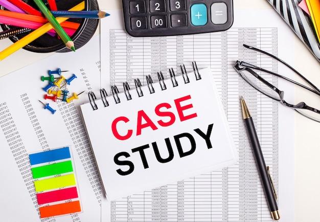 Na stole raporty, kalkulator, kredki i naklejki, długopis i zeszyt z napisem case study