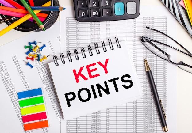 Na stole raporty, kalkulator, kredki i naklejki, długopis i zeszyt z napisem kluczowe punkty