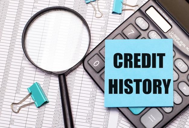 Na stole raporty, lupa, kalkulator i niebieska nalepka z napisem historia kredytów