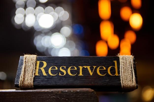 Na stole restauracyjnym tablica z napisem reserved