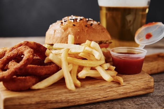 Na stole różne rodzaje fastfoodów i przekąsek oraz szklanka piwa. niezdrowe i niezdrowe jedzenie.