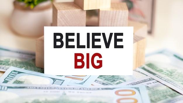 Na stole są dolary i znak, na którym jest napisany, wierzę, że jest duży