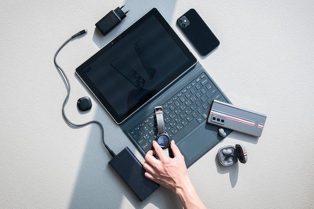 Na stole są laptopy, telefony komórkowe, słuchawki, ładowarki i zegary