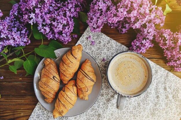 Na stole są spokojne rogaliki i filiżanka cappuccino. bukiet bzu na drewnianym stole.
