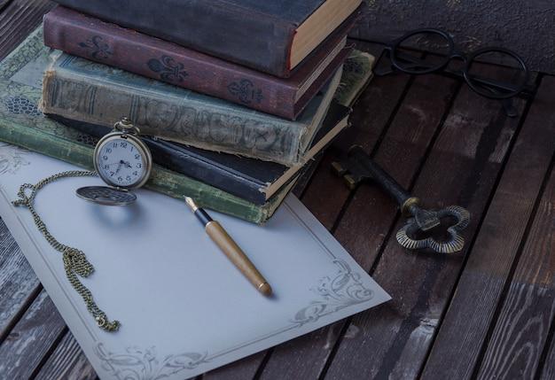 Na stole są stare książki, zegarki kieszonkowe, wieczne pióro, szklanki i papier do pisania