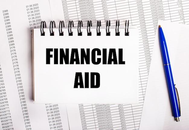 Na stole są wykresy i raporty, na których leży niebieski długopis i notatnik z napisem financial aid