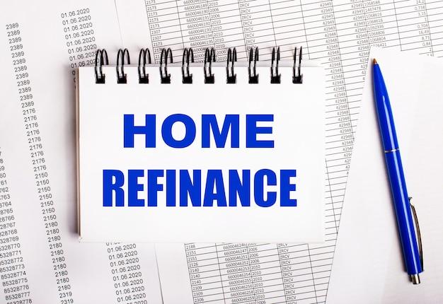 Na stole są wykresy i raporty, na których leży niebieski długopis i notes z napisem home refinance