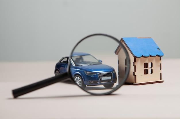 Na stole samochód, dom i szkło powiększające. koncepcja wyszukiwania domu i samochodu
