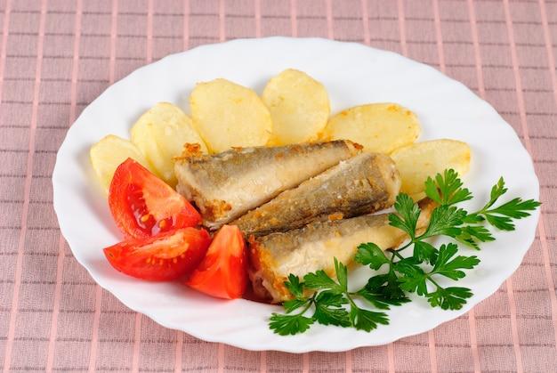 Na stole smażona ryba i ziemniaki