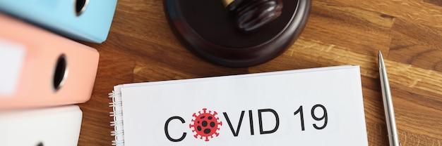 Na stole stoi drewniany młotek sędziowski i dokument z napisem covid -19