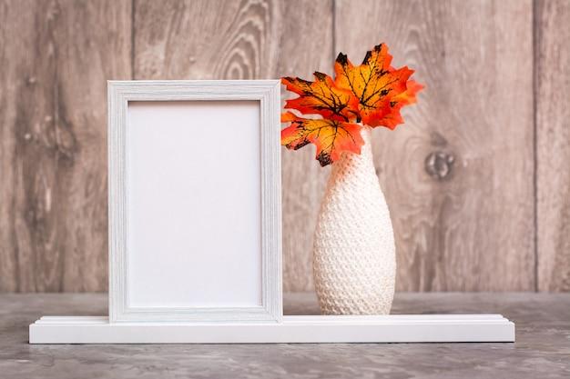 Na stole stoi pusta ramka na zdjęcie i wazon z pomarańczowymi liśćmi klonu. kolorystyka biało-pomarańczowo-beżowa. skopiuj miejsce