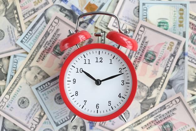 Na stole stoją amerykańskie rachunki z czerwonym budzikiem. znaczenie szybkości i precyzji w koncepcji biznesowej