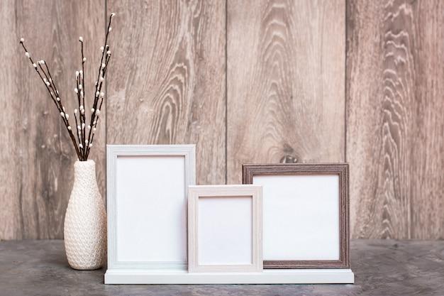 Na stole stoją trzy puste ramki na zdjęcia i wazon ze sztucznymi gałązkami wierzby. gama kolorów biało-szaro-beżowych. skopiuj miejsce