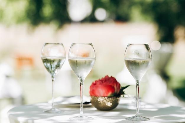 Na stole stoją trzy szklanki z wodą i czerwoną peonią