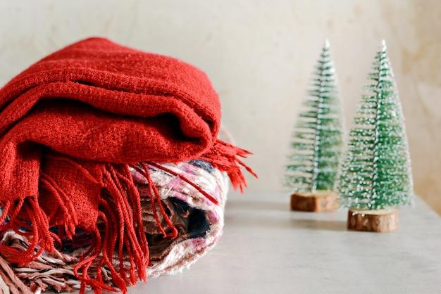 Na stole stos ciepłych ubrań. świąteczna atmosfera w domu. pokój ozdobiony jodłowymi gałęziami z szyszkami. styl życia. martwa jesień lub zima. domowa atmosfera, odzież zimowa.