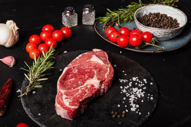 Na stole surowy antrykot wołowy z rozmarynem, solą i pieprzem na okrągłym łupku.