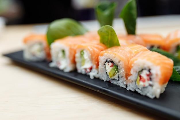Na stole sushi roll jedzenie ryba philadelphia japoński łosoś pyszne sushi ryż mączka ogórek tradycyjne wasabi świeże zdrowe wyśmienite dania surowe.