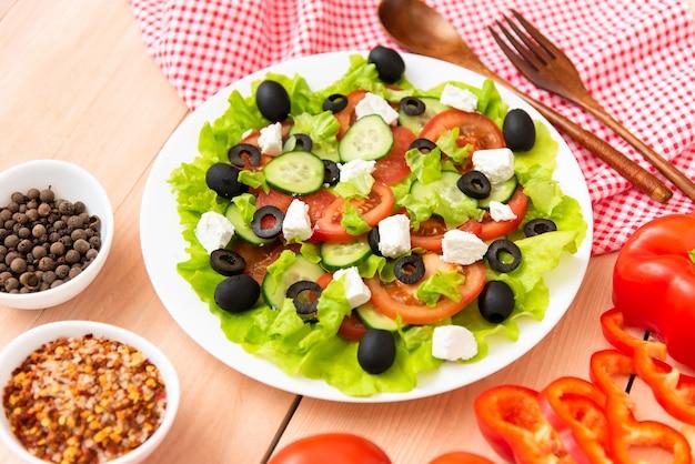 Na stole talerz świeżo przygotowanej sałatki greckiej i sera feta.