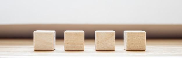 Na stole ułożone są cztery kwadratowe klocki drewna. do wykonania banerów służy drewniany klocek z miejscem na kopię na tekst lub symbole. panorama transparent tło z miejsca na kopię.