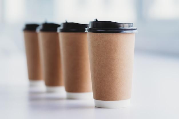 Na stole ustawiono cztery filiżanki kawy w rzędzie