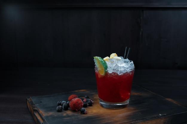 Na stole w barze owocowy słodki alkoholowy czerwony koktajl z lodem z syropem jagodowym i wódką w kryształowym kieliszku. koktajl ozdobiony świeżymi malinami i jagodami.