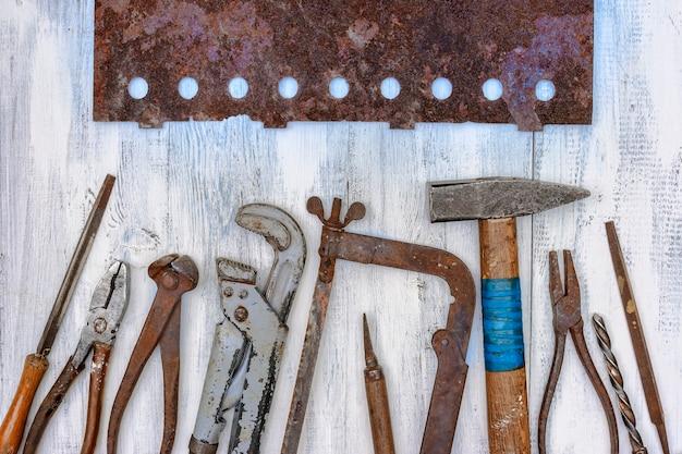 Na stole warsztatowym leżą stare zardzewiałe narzędzia