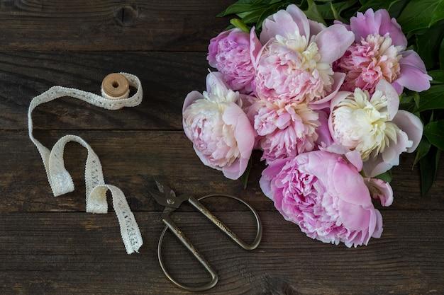 Na stole z ciemnego drewna bukiet różowych piwonii, nożyczek i koronkowej taśmy