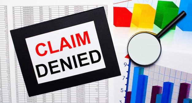 Na stole znajdują się doniesienia o wielokolorowych wykresach, lupie i kartce papieru w czarnej ramce z napisem claim denied. pomysł na biznes