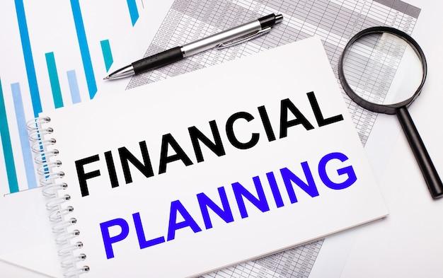 Na stole znajdują się raporty, wykresy, długopis, lupa i biały notes z tekstem planowanie finansowe. pomysł na biznes