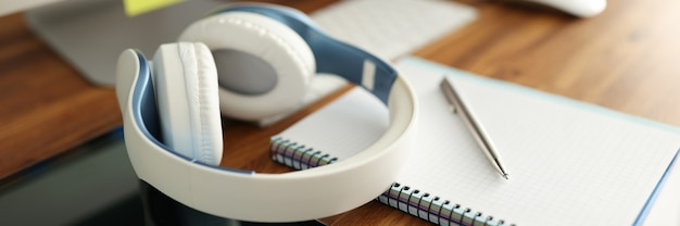 Na stole znajdują się słuchawki, tablet oraz pamiętnik z długopisem. koncepcja zdalnego uczenia się i szkolenia