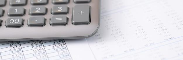 Na stole znajduje się długopis kalkulatora i dokument z koncepcją usług księgowych raportów finansowych