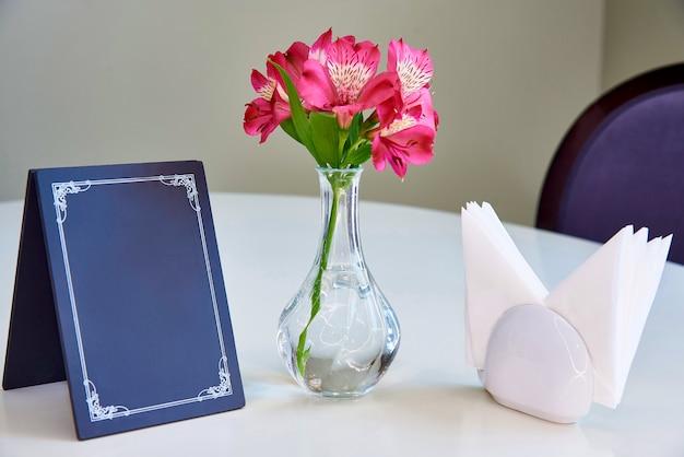 Na stole znajduje się niebieska tabliczka znamionowa, wazon ze świeżymi liliami i serwetkami.