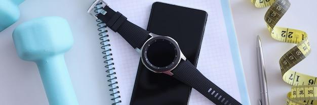 Na stole znajduje się planer dnia smartfon, inteligentny zegarek, hantle i centymetrowa kontrola kalorii oraz