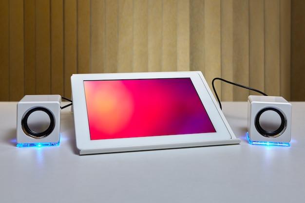 Na stole znajduje się tablet zamontowany na uchwycie do tabletu i podłączony do dwóch małych białych głośników z oświetleniem led.