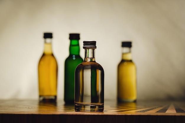 Na stoliku na świetle stoją różne butelki z alkoholem