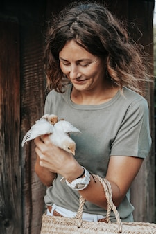 Na swoim podwórku opiekunka opiekuje się nowo narodzonymi żółtymi kurczakami. gospodarstwo domowe