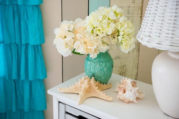 Na szafce nocnej stoi biała lampa i wazon z kwiatami.