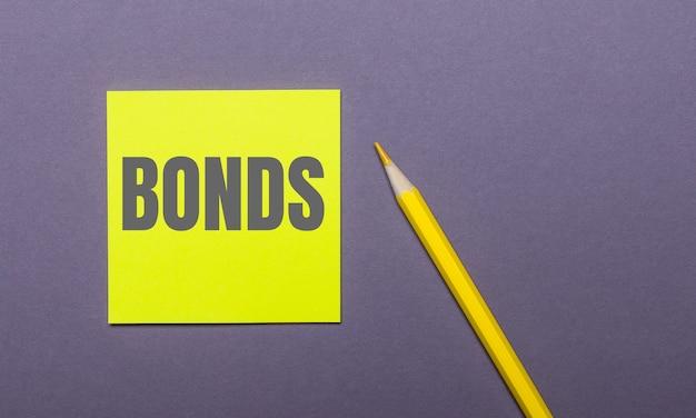 Na szarej powierzchni jasnożółty ołówek i żółta naklejka z napisem bonds