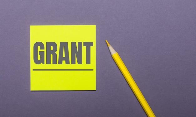 Na szarej powierzchni jasnożółty ołówek i żółta naklejka z napisem grant