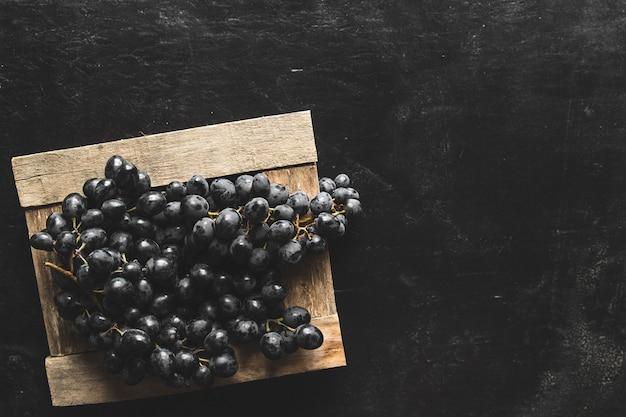 Na szarej ścianie ciemne winogrona w drewnianym pudełku