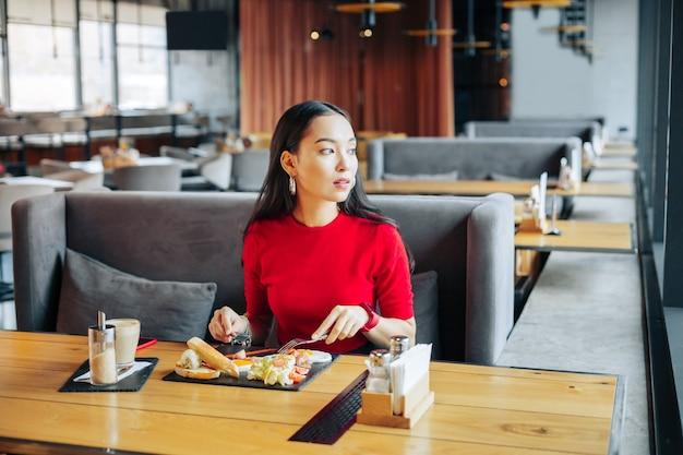 Na szarej sofie ciemnowłosa kobieta siedzi na szarej sofie w restauracji delektując się lunchem
