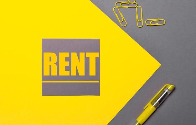 Na szaro-żółtej powierzchni szara naklejka z żółtym napisem rent, żółte spinacze biurowe i żółty długopis