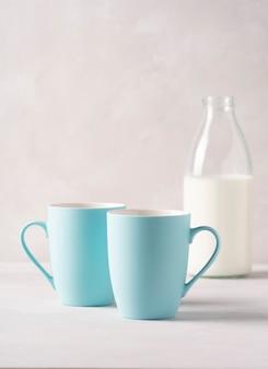 Na szarym betonowym stole stoją dwa niebieskie kubki i butelka mleka.