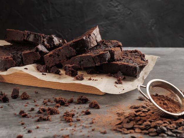 Na szarym stole stoi pokrojony czekoladowy placek z kawałkami czekolady i kakao.