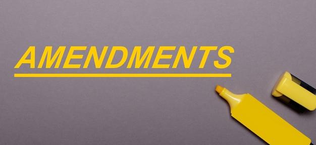 Na szarym tle żółty znacznik i żółty napis poprawki