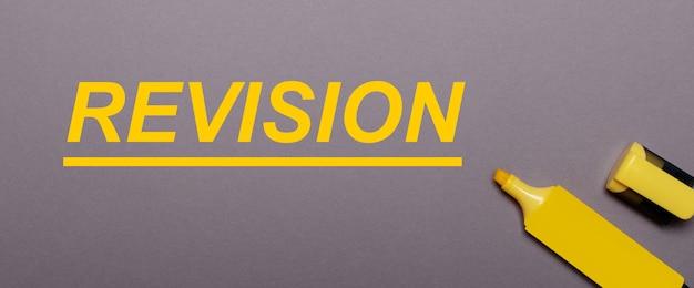 Na szarym tle żółty znacznik i żółty napis revision