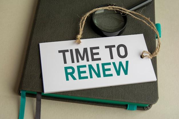 Na szarym zeszycie znajduje się lupa i biała kartka z napisem time to renew, selektywne skupienie