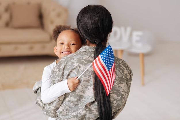 Na szczęście jestem z tobą. uśmiechnięte słodkie kręcone dziewczyny wyglądające na szczęśliwe, gdy przytulają matkę po tym, jak nie widzieli jej przez jakiś czas