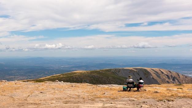 Na szczycie parku przyrody serra da estrela, portugalia, z dwiema osobami bez twarzy, siedzącymi i siedzącymi i obserwującymi piękno krajobrazu, bez twarzy, z tyłu