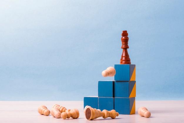 Na szczycie schodów z niebieskimi kostkami jest król szachowy. na dole znajdują się inne figury szachowe. pojęcie sukcesu w biznesie, motywacja, konkurencja
